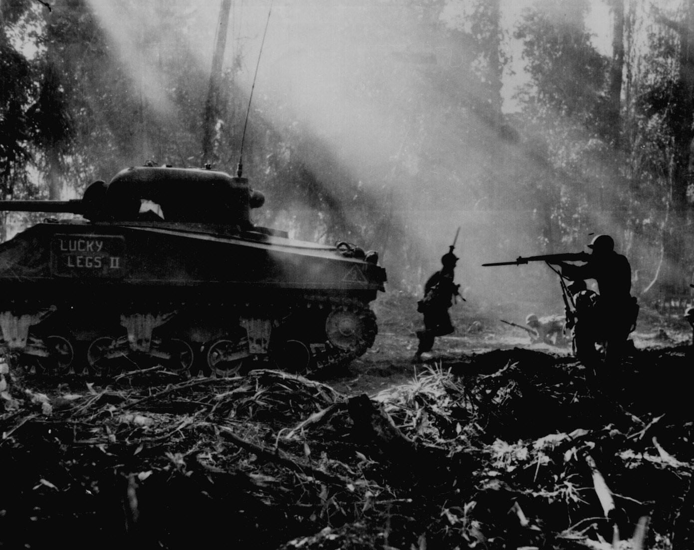 [Photo] American troops advanced under the cover of M4 Sherman tank 'Lucky Legs II' during mop up operations on Bougainville, Solomon Islands, Mar 1944 | World War II Database