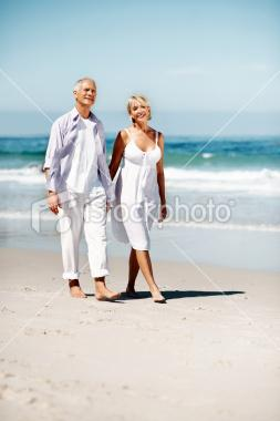 Couple walking along the beach | Stock Photo | iStock