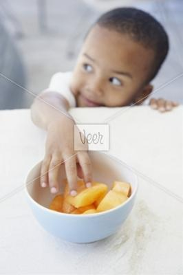 Boy reaching for honeydew Stock Photo - Veer.com
