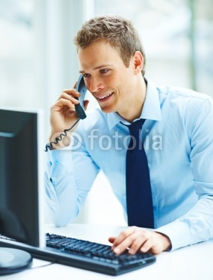 Photo: Young busineass man speaking on the phone while working on a com © Yuri Arcurs #12376896