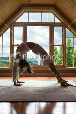 Young Woman in Bridge Yoga Position Inside | iStock